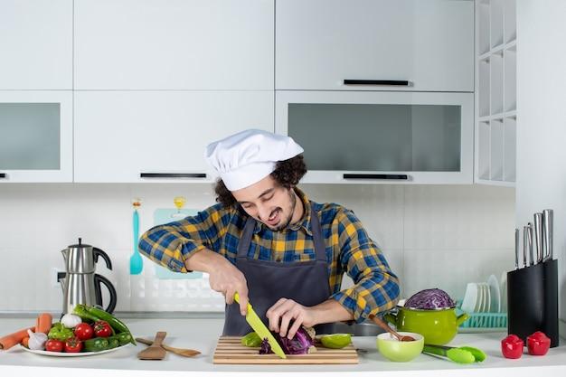 Vista frontale dello chef sorridente con verdure fresche che tagliano gli alimenti nella cucina bianca