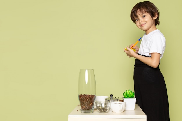 A front view smiling child boy in white t-shirt preparing coffee drink on the table on the stone colored desk