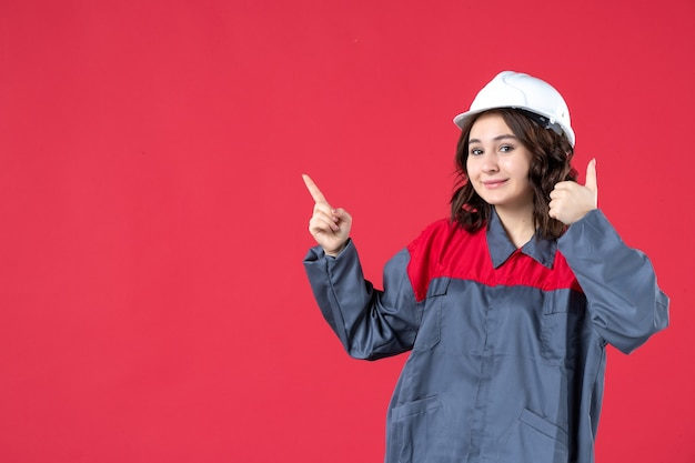 Front view of smiling confident female builder in uniform with hard hat and making ok gesture pointing up on isolated red background