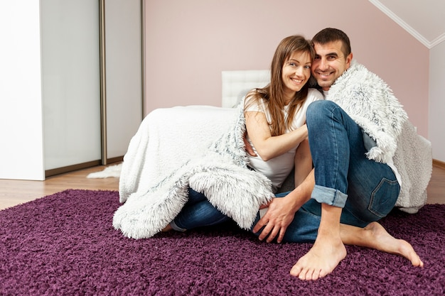 Front view smiling couple covering with a blanket