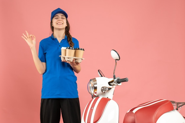 Front view of smiling courier girl standing next to motocycle holding coffee making eyeglasses gesture on pastel peach color background
