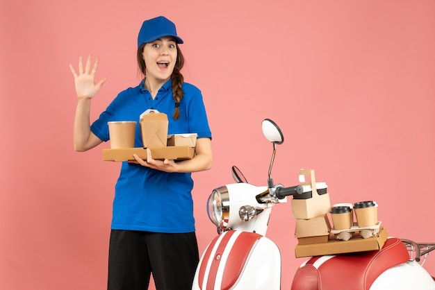 Front view of smiling courier girl standing next to motorcycle holding coffee and small cakes showing five on pastel peach color background