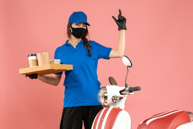 Front view of smiling courier girl wearing medical mask gloves standing next to motorcycle holding coffee small cakes on pastel peach color background
