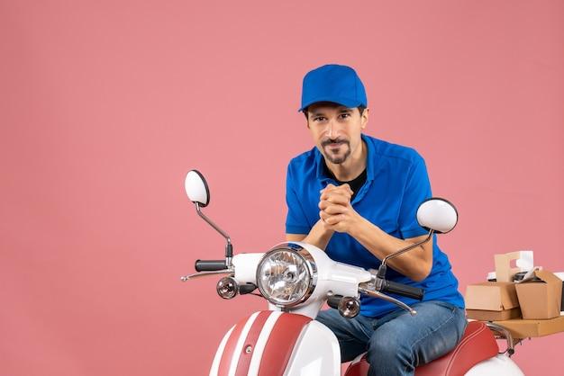 Vista frontale del corriere sorridente che indossa un cappello seduto su uno scooter su sfondo color pesca pastello