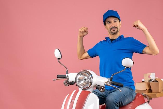 Vista frontale del corriere sorridente che indossa un cappello seduto su uno scooter che mostra il suo muscoloso su sfondo color pesca pastello