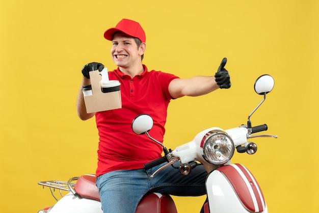 Vista frontale del corriere sorridente uomo che indossa camicetta rossa e guanti cappello in maschera medica consegna ordine seduto su scooter tenendo gli ordini con il pollice in alto