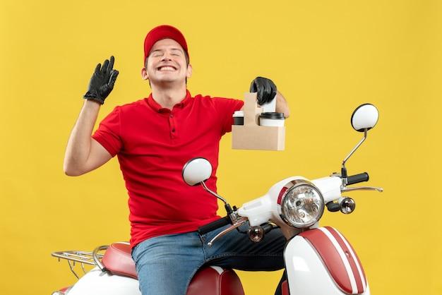 Vista frontale dell'uomo sorridente del corriere che indossa guanti rossi della camicetta e del cappello nella mascherina medica che trasporta l'ordine che si siede sugli ordini della tenuta dello scooter