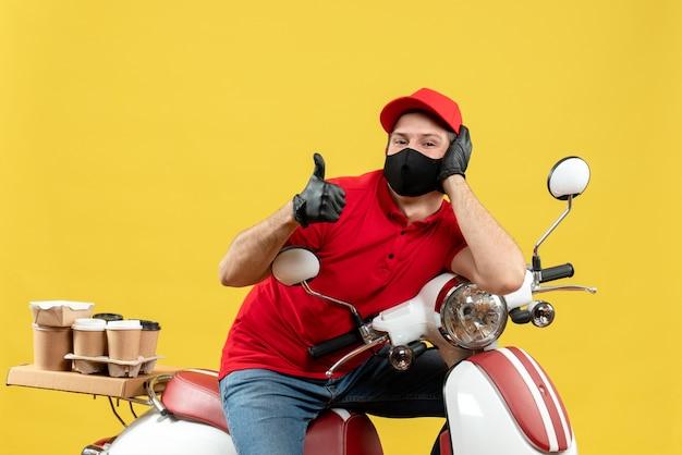 Vista frontale dell'uomo sorridente del corriere che indossa guanti rossi della camicetta e del cappello nella mascherina medica che trasporta l'ordine che si siede sul motorino che fa gesto giusto