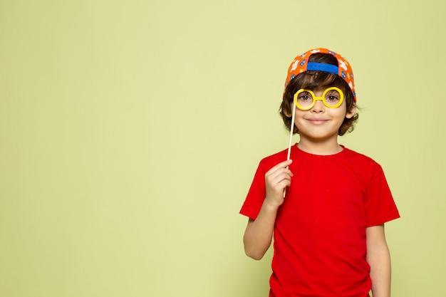 Un ragazzo sveglio sorridente di vista frontale adorabile in maglietta rossa sullo spazio colorato pietra