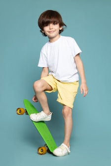 A front view smiling cute child sweet adorable in white t-shirt holding skateboard on the blue space
