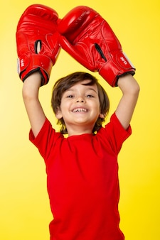 A front view smiling cute kid in red t-shirt and red boxing gloves on the yellow wall