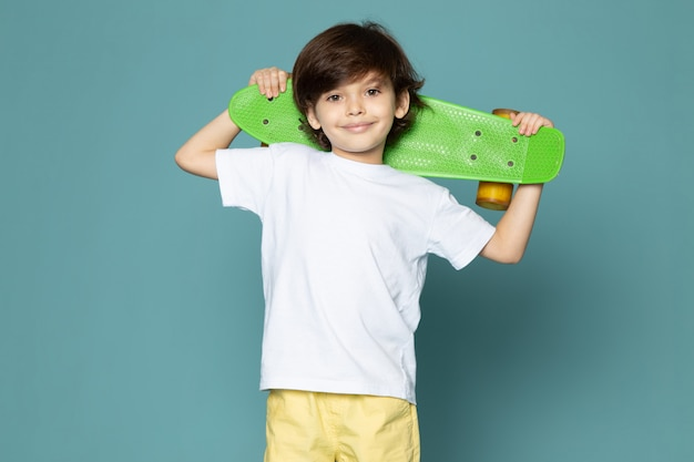 A front view smiling cute kid in white t-shirt holding skateboard on the blue floor