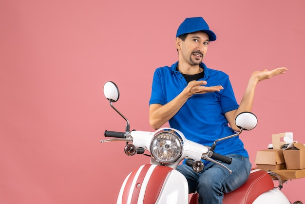 Front view of smiling delivery guy wearing hat sitting on scooter and pointing something on the left side on pastel peach background