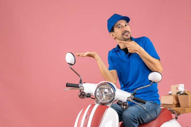 Front view of smiling delivery guy wearing hat sitting on scooter and pointing something on the right side on pastel peach background