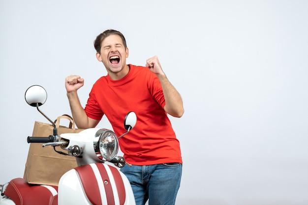 Vista frontale dell'uomo di consegna sorridente in uniforme rossa che sta vicino al motorino che si sente molto felice su priorità bassa bianca