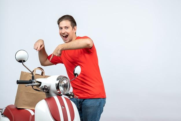 Vista frontale dell'uomo di consegna sorridente in uniforme rossa che sta vicino all'ordine di puntamento del motorino su priorità bassa bianca