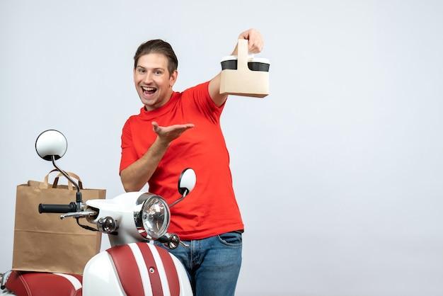 Vista frontale dell'uomo di consegna sorridente in uniforme rossa che sta vicino allo scooter che mostra l'ordine che indica in avanti su fondo bianco