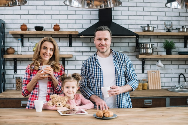 Front view of smiling family having breakfast in kitchen