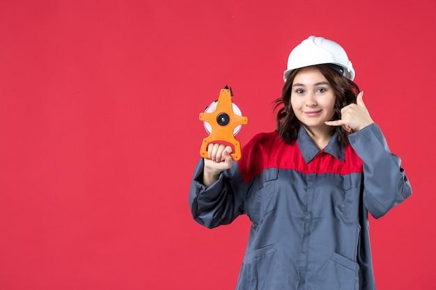 Vista frontale dell'architetto donna sorridente in uniforme con elmetto che tiene il nastro di misurazione e mi fa un gesto di chiamata su sfondo rosso isolato