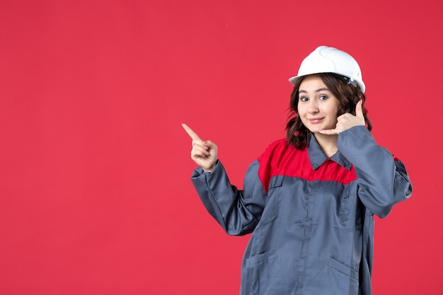 Front view of smiling female builder in uniform with hard hat and making call me gesture pointing up on isolated red background