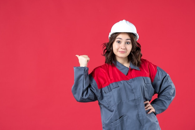 Front view of smiling female builder in uniform with hard hat and making ok gesture on isolated red background