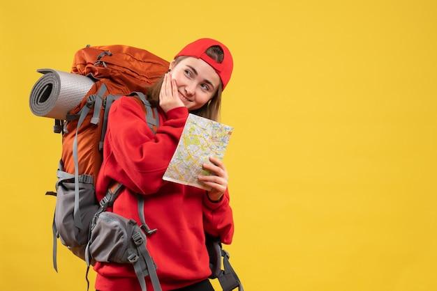 Вид спереди улыбающаяся женщина-турист с красным рюкзаком, держащая карту путешествий