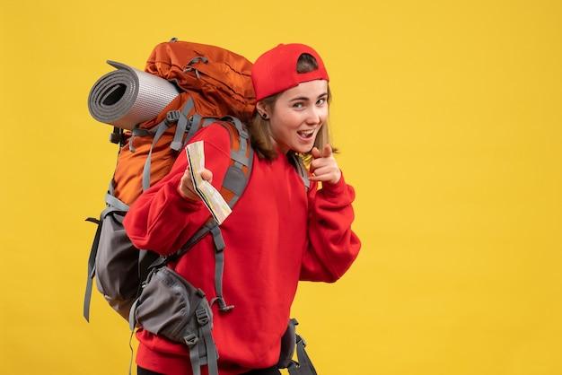 Вид спереди улыбающаяся туристка с большим рюкзаком, держащая карту