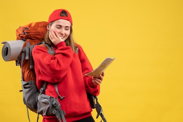Viandante femminile sorridente di vista frontale con lo zaino rosso che esamina mappa
