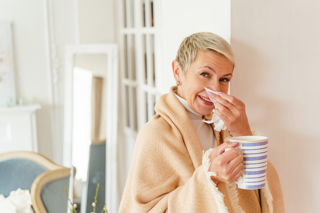 Front view of a smiling female with a mug of tea and a paper tissue looking forward