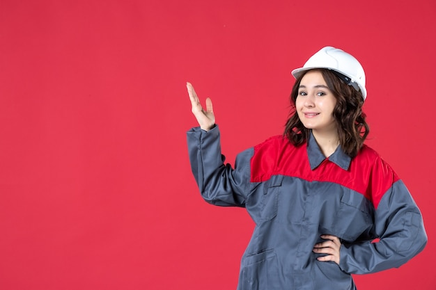 Front view of smiling focused female builder in uniform with hard hat and pointing up on isolated red background