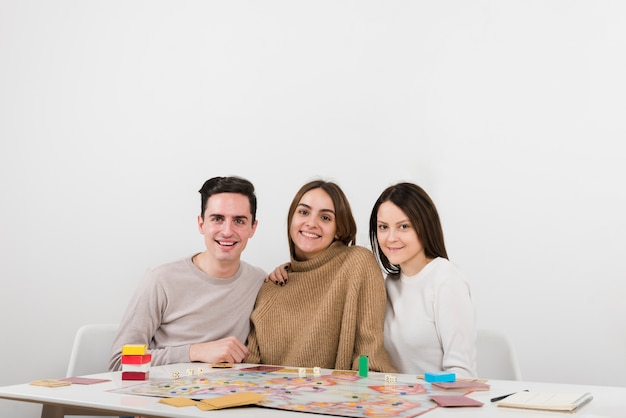 Front view smiling friends playing a board game