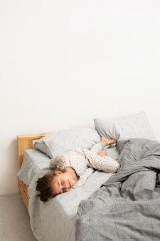 Front view of smiling girl in bed with copy space