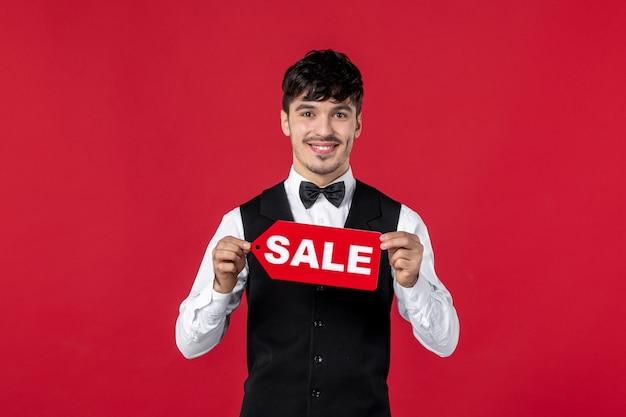 Vista frontale del cameriere sorridente in uniforme con farfalla sul collo che tiene l'icona di vendita su sfondo rosso isolato