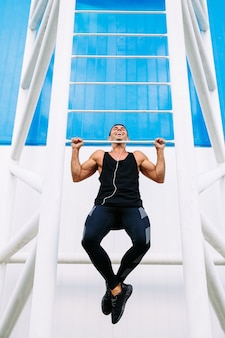 Front view of smiling handsome muscular guy doing pull ups, wearing black sportswear.