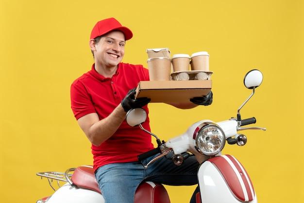 Vista frontale dell'uomo sorridente felice del corriere che indossa guanti rossi del cappello e della camicetta nella mascherina medica che trasporta l'ordine che si siede sugli ordini della tenuta dello scooter