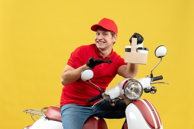 Vista frontale dell'uomo sorridente felice del corriere che indossa guanti rossi della camicetta e del cappello nella mascherina medica che trasporta l'ordine che si siede sugli ordini di puntamento del motorino