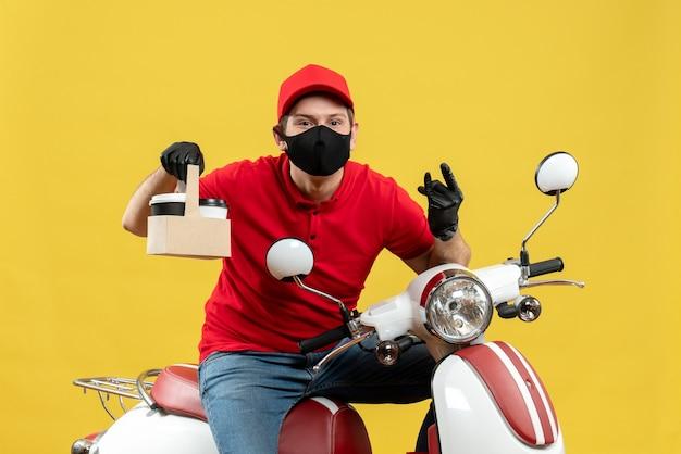 Vista frontale dell'uomo sorridente felice del corriere che indossa guanti rossi del cappello e della camicetta nella mascherina medica che si siede sullo scooter che mostra gli ordini