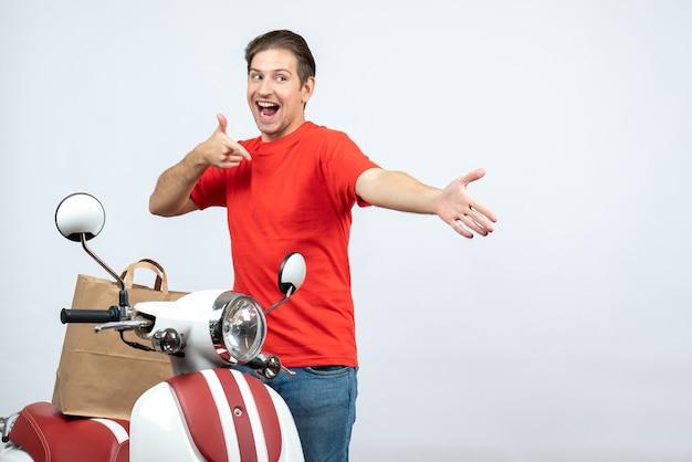 Vista frontale dell'uomo di consegna orgoglioso felice sorridente in uniforme rossa che sta vicino al motorino su fondo bianco