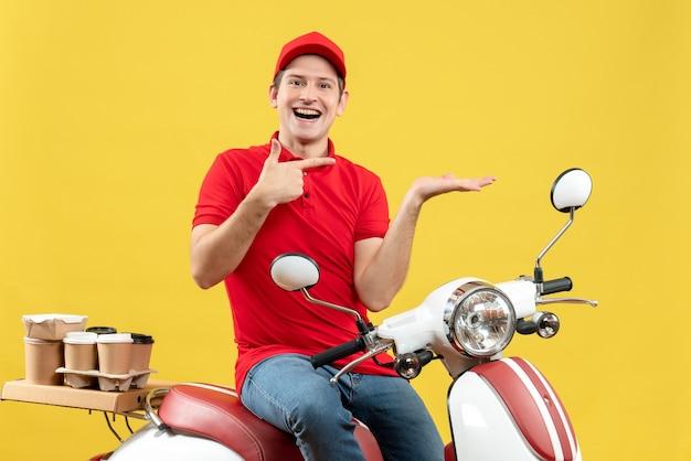 Vista frontale del giovane ragazzo sorridente e felice che indossa la camicetta rossa e il cappello che consegna gli ordini che indicano qualcosa sul lato sinistro su sfondo giallo