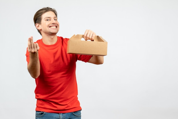 Front view of smiling happy young man in red blouse holding box on white background