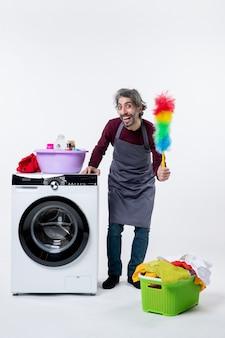 Uomo sorridente della governante di vista frontale che tiene lo spolverino in piedi vicino al cesto della biancheria della lavatrice sul muro bianco