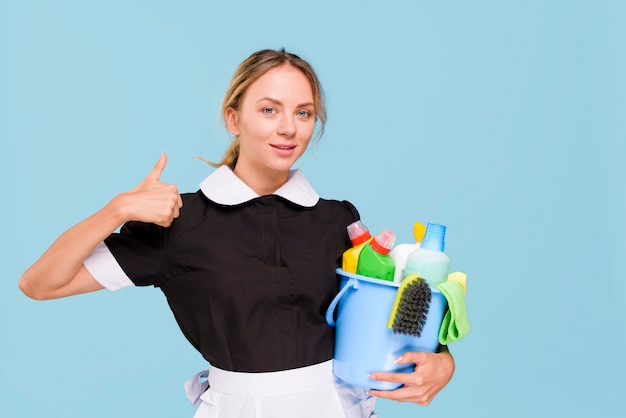 Front view of smiling janitor woman showing thumb up sign while holding cleaning products in bucket