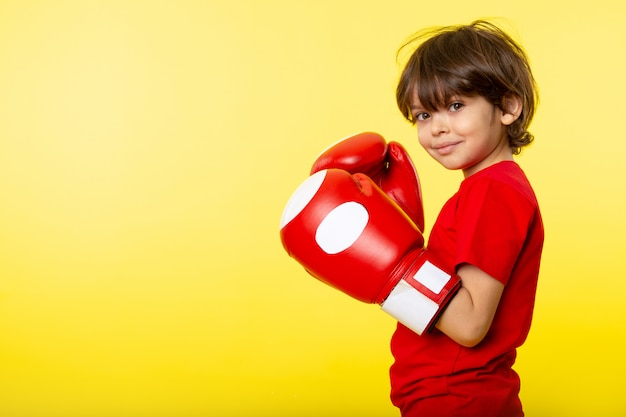 A front view smiling kid in red t-shirt and red gloves boxing on the yellow wall