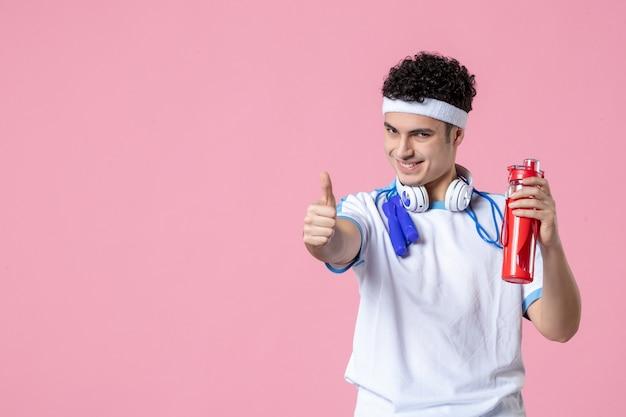Вид спереди улыбающегося спортсмена в спортивной одежде с бутылкой воды