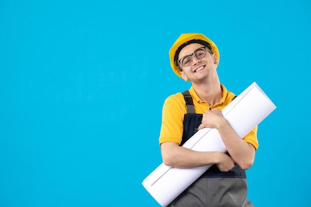 Vista frontale del costruttore maschio sorridente in uniforme gialla con piano di carta sull'azzurro