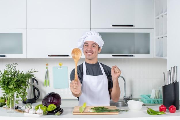 台所のテーブルの後ろに木のスプーンを保持している制服を着た男性シェフの笑顔の正面図