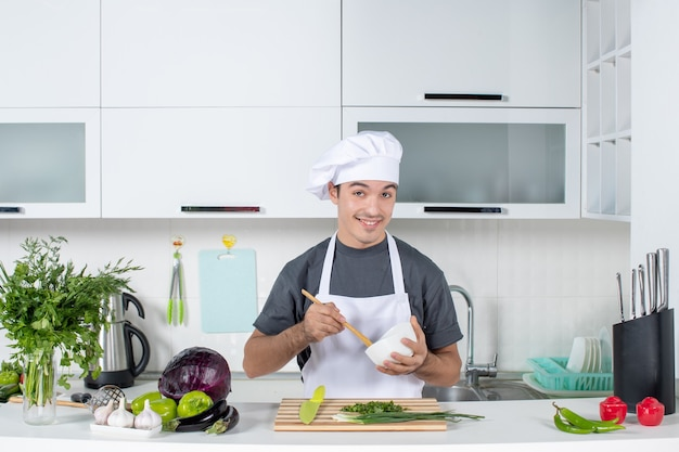 Front view smiling male chef in uniform holding bowl and spoon behind kitchen table