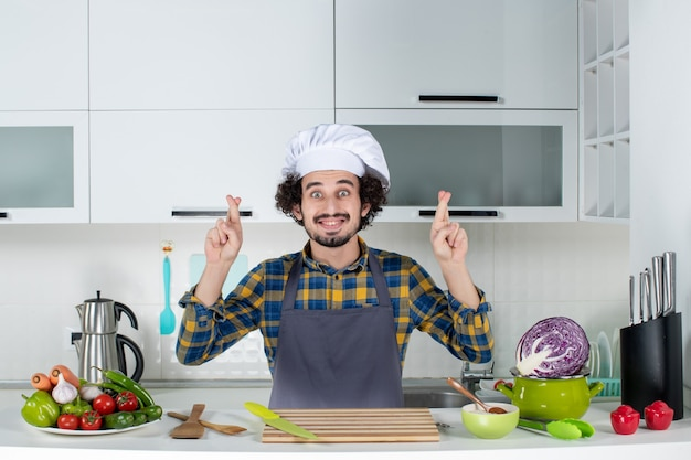Front view of smiling male chef with fresh vegetables and cooking with kitchen tools and crossing his fingers in the white kitchen