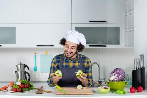 Vista frontale dello chef maschio sorridente con verdure fresche e cucina con utensili da cucina e tenendo i peperoni verdi tagliati nella cucina bianca