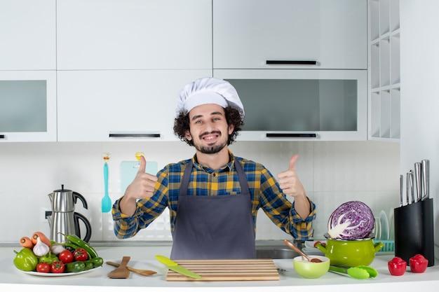 Vista frontale dello chef maschio sorridente con verdure fresche e cucinare con utensili da cucina e fare un gesto ok nella cucina bianca